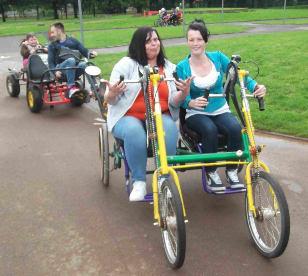Two women using a tandem handcycle