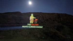 Projection of 'This machine fights Climate Change' on Salisbury Crags